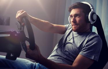 man playing car racing video game at home