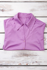Folded purple women shirt. White wooden desks surface background.