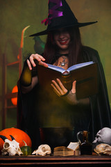 Portrait of witch in black hat and with black book brewing potion