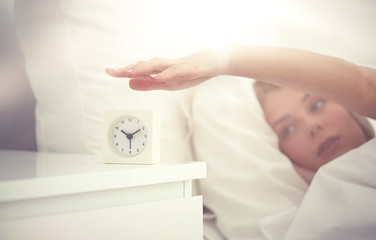 Fototapete - close up of woman with alarm clock in bed at home