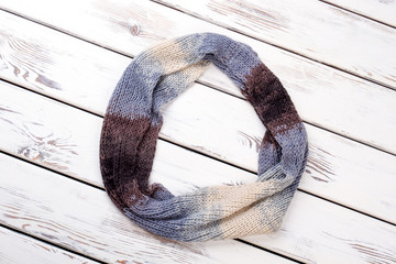 Colourful rounded woolen scarf. White wooden desks surface background.
