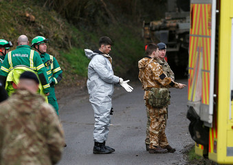 Soldiers wearing protective suits and members of the emergency services work at a site in Winterslow, near Salisbury
