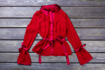 Stylish polyester red jacket. Flat lay, grey wooden surface background. Fotomurales