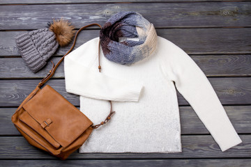 Layout clothing for cold winter. White sweater, handbag, hat with bombom and scarf.
