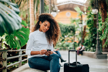 Beaituful female tourist with curly hair using smartphone. Sitting outdoors with suitcase.