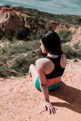 Sporty woman sitting on hill