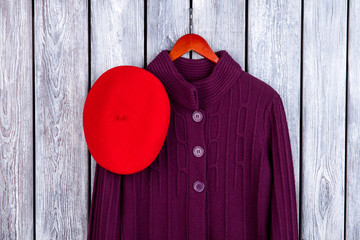 Winter women's coat and hat. Top view wool knitted coat on hanger and red beret. Dark wooden desk surface background.
