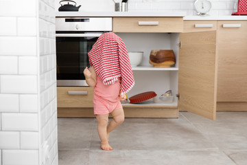 Baby boy walking in the kitchen with towel over head