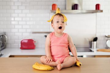 Baby making goofy face with banana skin on his head
