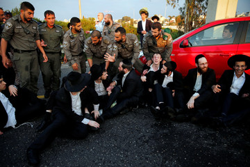 An Israeli ultra-Orthodox Jew block a main road in Israel before security forces evacuate them during a protest against the detention of a member of his community who refuses to serve in the Israeli army, in Bnei Brak