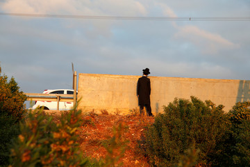 An Israeli ultra-Orthodox Jew looks over a wall as demonstrators block a road during a protest against the detention of a member of his community who refuses to serve in the Israeli army, in Bnei Brak
