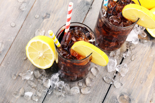 Softdrink with ice cubes, lemon and straw in glass.
