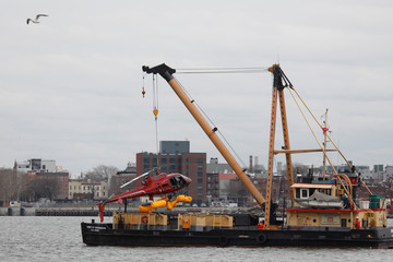 The wreckage of a chartered Liberty Helicopters helicopter that crashed into the East River is hoisted from the water in New York