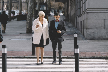 Man and woman with mobile phone cross the road.