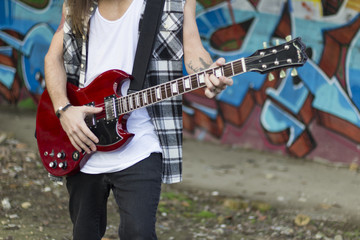 young man with long hair playing on a guitar