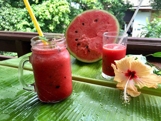 Healthy watermelon smoothie on a banana leaf background