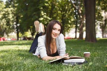 Young woman reading book lyinf in park