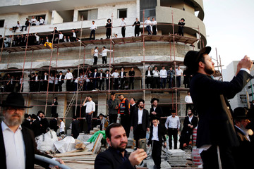 Israeli ultra-Orthodox Jewish men look on during a protest against the detention of a member of his community who refuses to serve in the Israeli army, in Bnei Brak