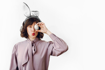 beautiful stylish girl in bunny ears holding easter egg with funny emotions on white background isolated with space for text. funny easter hunt concept. happy woman  with egg at face