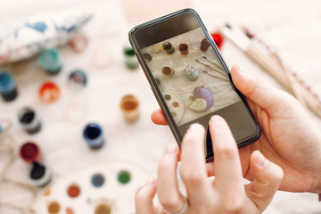 instagram and blogging photography concept. hands holding phone and taking picture of easter flat lay with colorful eggs and paint on table. happy easter concept