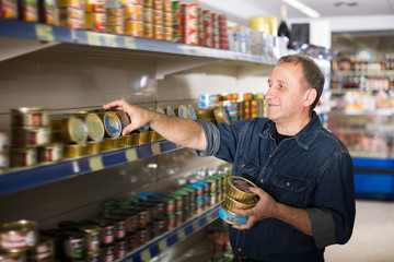 Portrait of mature man buying a preserves