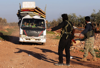 Internally displaced people are seen in a truck in the town of Inab