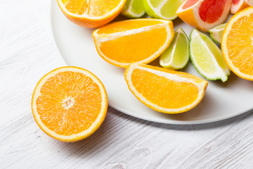 plate with cut citrus fruits on white wooden background