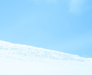 Fabulous white mountain on blue sky background in winter. The descent is steep.