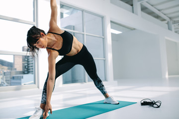 Fitness woman in Utthita Trikonasana pose at gym
