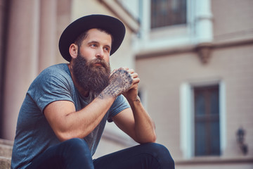 A handsome hipster male with a stylish beard with a tattoo on hi