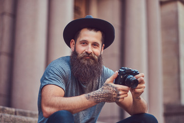 A handsome hipster male with a stylish beard and tattoo on his a