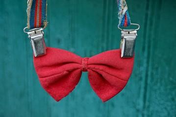 красный старый галстук-бабочка на подтяжках на зелёном фоне