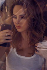 Portrait of a young attractive woman making selfie photo on smartphone, view fthrough window glass