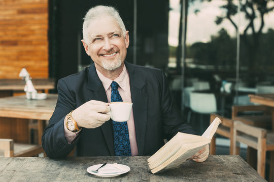 Boss Enjoying Reading Book and Drinking Coffee