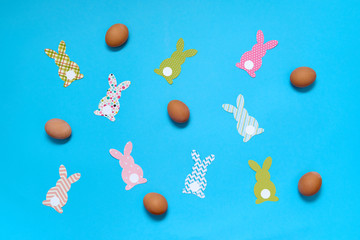 Easter bunny decoration and eggs on blue background, copy space. DIY holiday handicraft of colorful rabbits. Flat lay, top view. Paper rabbits cutouts. Easter greeting card. Happy Easter concept