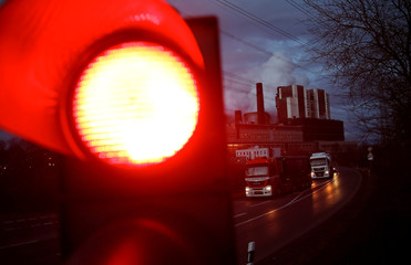 A traffic light signals red in front of the Weisweiler brown coal power plant of German energy supplier RWE