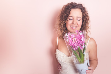 Beautiful curly woman in white dress with hyacinth flowers in hands on a light pink background. Hello spring concept.