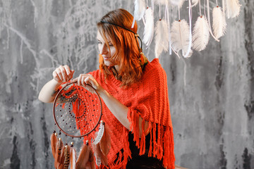Woman master creates an amulet dreamcatcher in her workshop, handmade boho decoration and magical crafted design concept