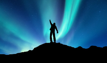 Silhouette of a winner on the northen light backgroun. Concept and idea of active life