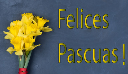 inscription Felices Pascuas with fresh flowers, on a wooden background