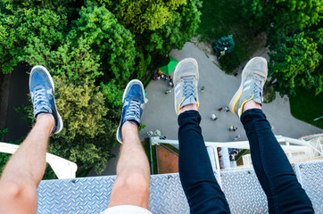 Feet Hanging in the Air First Person View. Above the City Park. Two People Riding a Ferris Wheel Top View