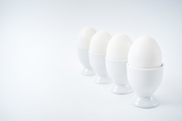 White eggs standing on egg cup isolated on white background, copy space. Row of boiled eggs in stand. Healthy food concept