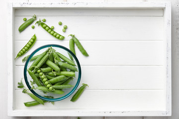 Pods of fresh green peas in glass bowl in white wooden tray, top view