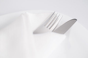 Fork and knife into white napkin on white plate