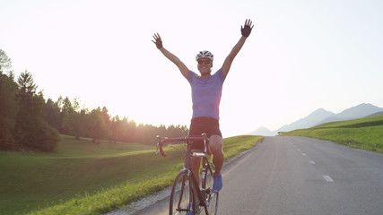 SUN FLARE: Pro cyclist cheerfully rides road bike with no hands after victory.