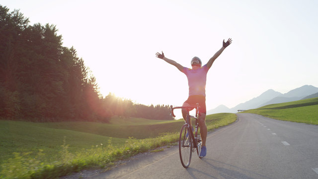 LENS FLARE Thrilled bicycle rider celebrates win in bike race across countryside