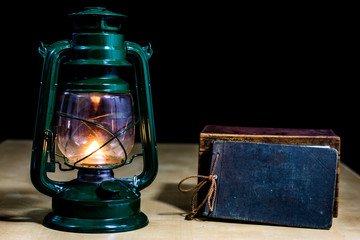 Old oil lamp and books lying on the table. A flame from an old source of light illuminating old prints.