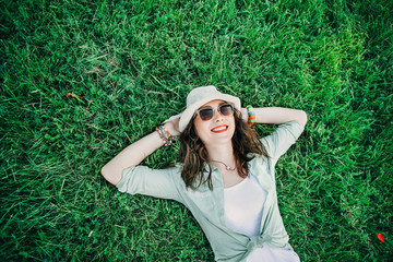 Trendy Hipster Girl Relaxing on the Grass . Summer holidays, vacation, travel and people concept - smiling young hippie woman