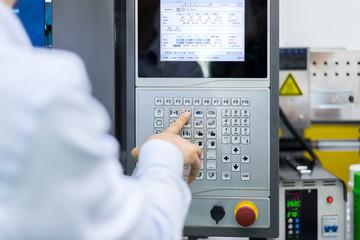 Mechanical technician operating program on control panel of high precision CNC machining center, machining die metal mold process