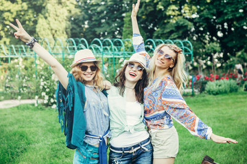 Summer holidays, vacation, travel and people concept - smiling young hippie women with guitar playing music. Funny time for the best friends. Lifestyle. Boho style.
